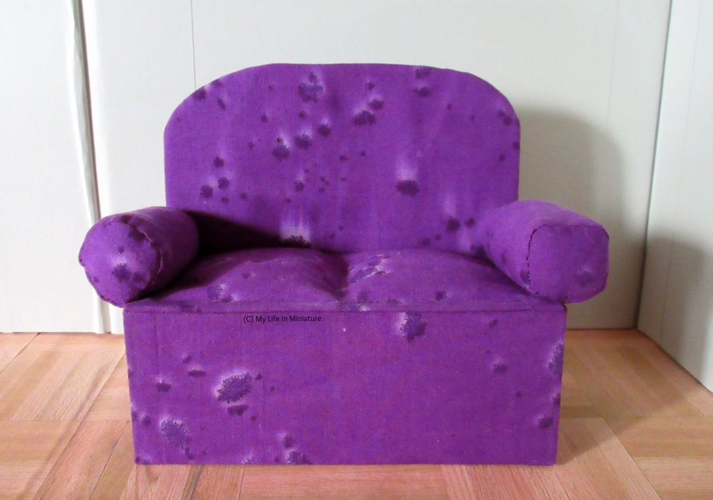 A small purple couch sits on a wood parquet floor and a grey background. The purple fabric of the couch has darker purple splotches on it in a batik fashion.