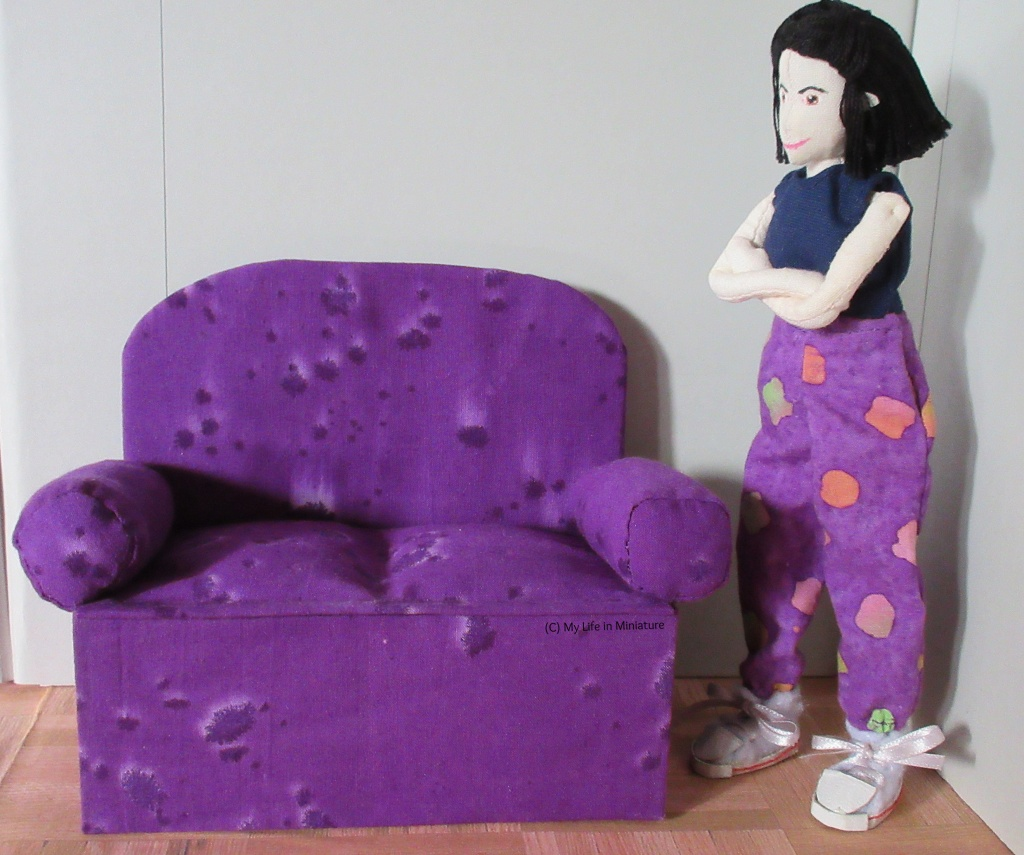 Tiffany stands to the side of the purple couch, arms folded in thought.