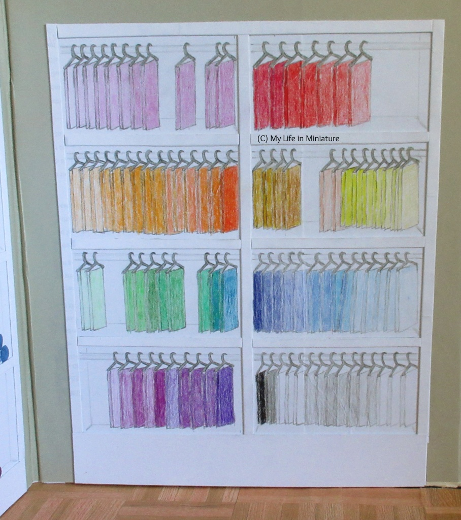 Full view of Needle & Thread's fat quarter shelves. The fabric is hanging from dark grey coat-hangers, with colours arranged in rainbow order from top left to bottom right.
