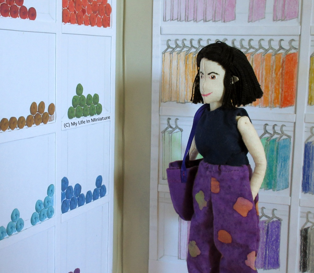 Tiffany stands in front of the two shelving units, looking at the yarn shelves. She has a hand in her pocket, a dark purple tote bag on her shoulder and a thoughtful expression.