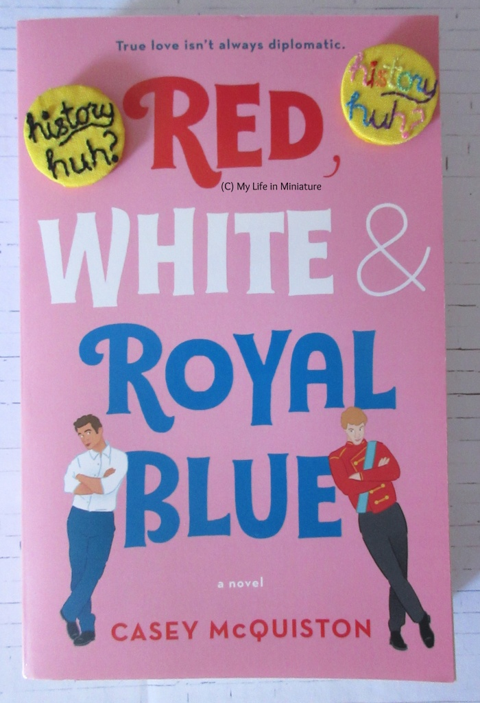 Overhead shot of 'Red, White and Royal Blue''s cover with the two badges in the top corners.
