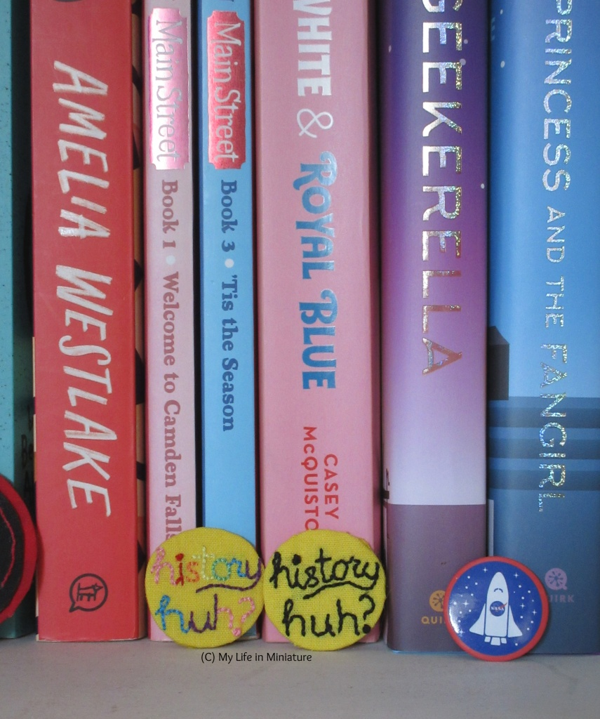 The two badges are leaning against the base of 'Red, White and Royal Blue's spine. Other spines can be seen beside the badges.