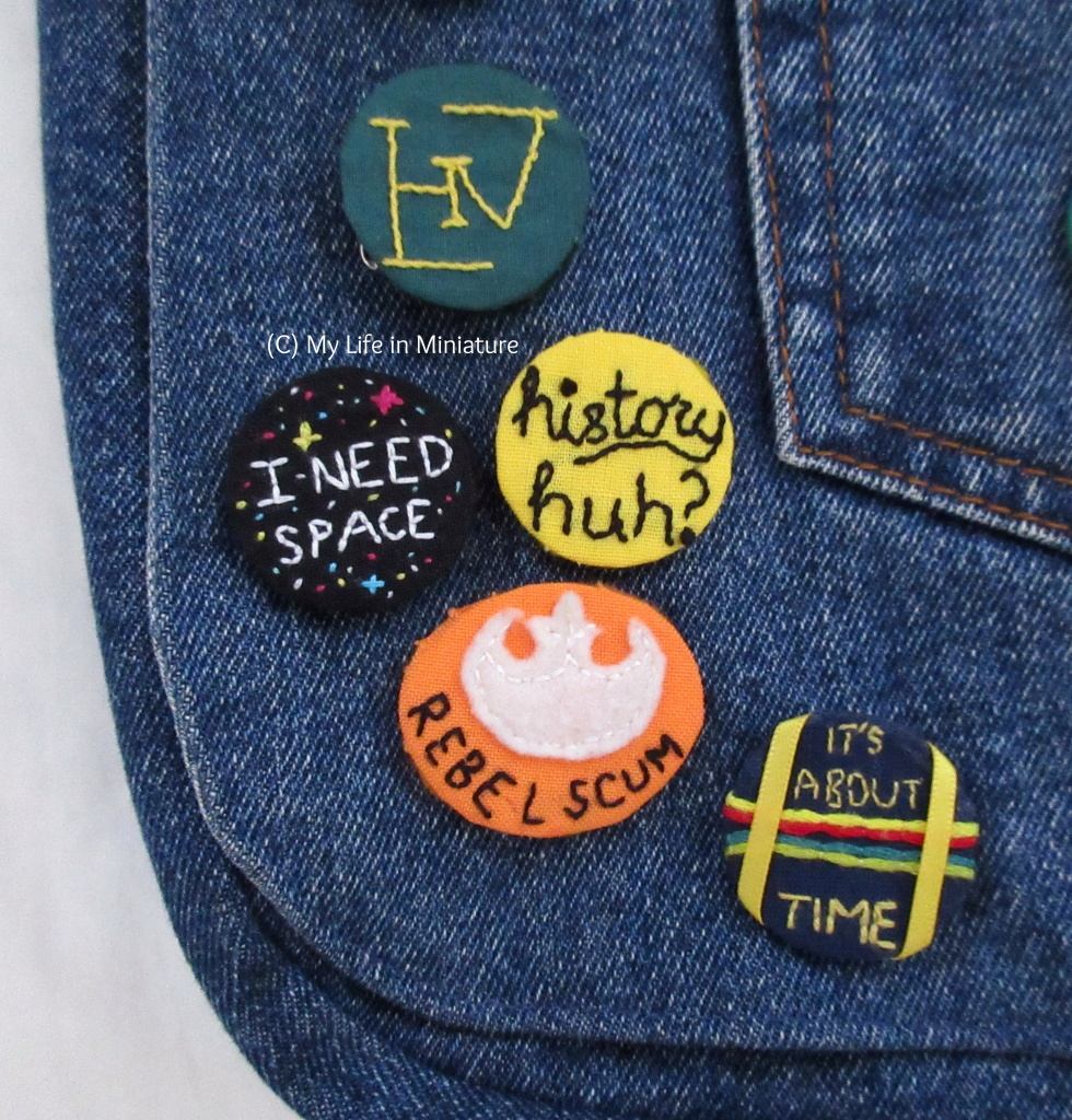 Overhead shot of a denim bag's bottom right corner, focused on a cluster of badges. All are embroidered - the black 'history, huh?' one is featured prominently.