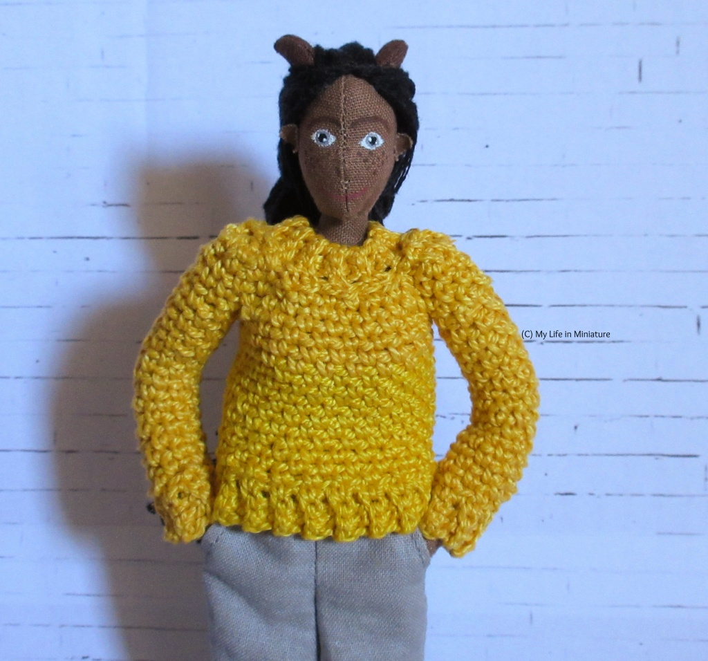 Petra stands with hands in pockets wearing a yellow crocheted jumper.