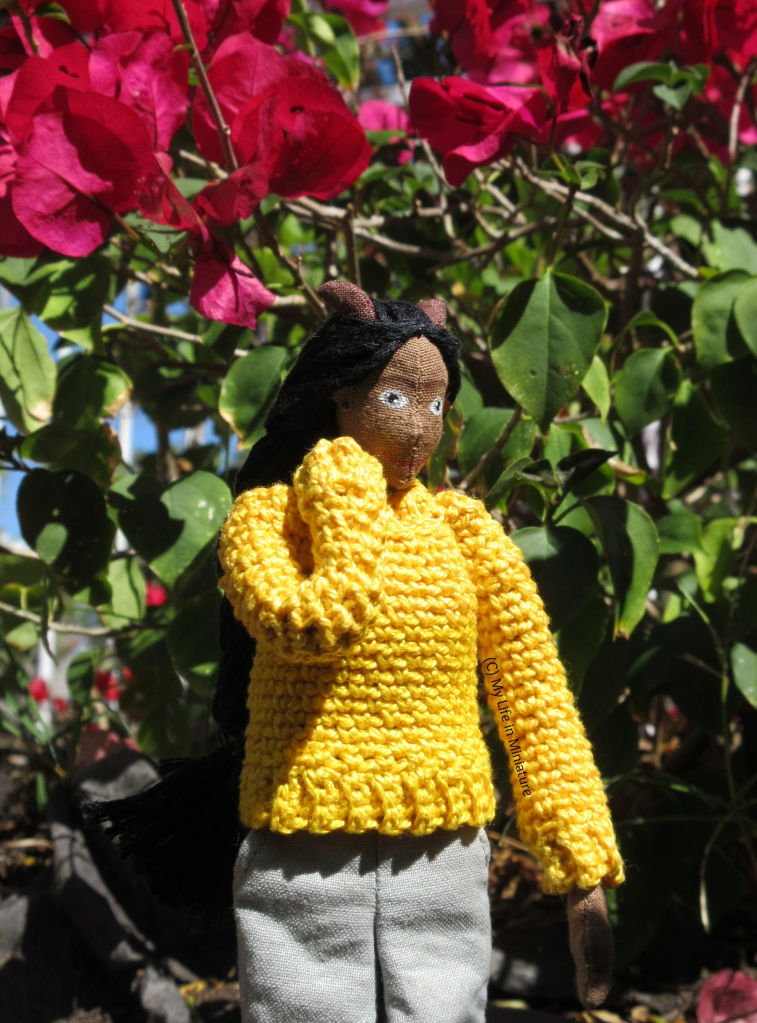 Petra stands in the sun under a hot pink bougainvillea plant. One hand is behind her neck and she looks to the right. She wears the yellow jumper.