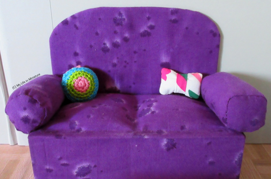 Needle & Thread's purple couch sits against a grey wall. A circular crocheted cushion sits in the left corner of the couch, coloured with three rings of pink, green and blue from the centre. A bow tie cushion sits in the other corner, coloured white with green and pink splotches.
