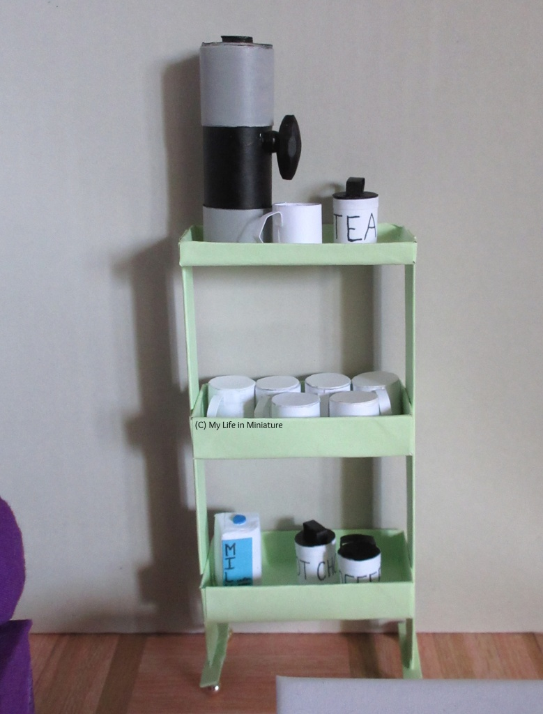The fully stocked drinks trolley stands against a pale grey background. Top shelf has a hot water urn with a mug under its spout, and a canister of tea. Middle shelf has six white mugs, upside-down. Bottom shelf has a carton of milk, a canister of hot chocolate and a canister of coffee.