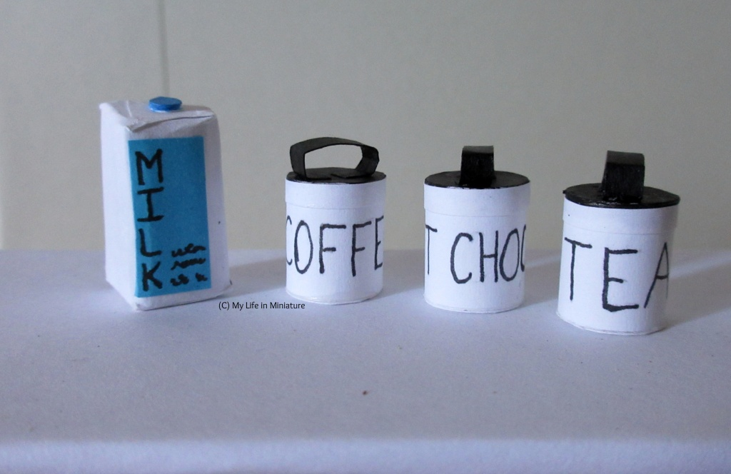 The three canisters and the milks it on a white surface. The milk carton is white with a blue label saying 'MILK' and a blue screw-on lid on top. The three canisters are white with black lids and their contents written on them in black.