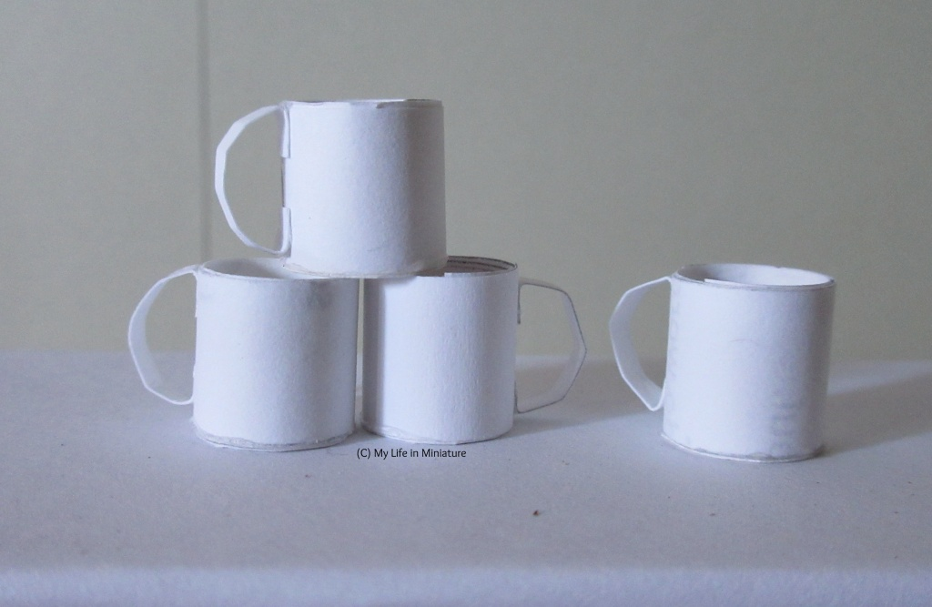 Four plain white mugs sit on a white surface. Three are stacked in a pyramid, and one sits to the right of the pyramid.
