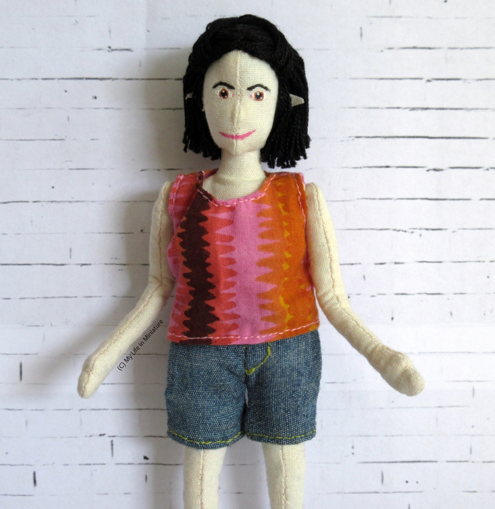 TIffany wears a pink, orange, red  and dark brown shirt and denim shorts in front of a white brick background. Her hands are spread in a 'ta-daa!' gesture.