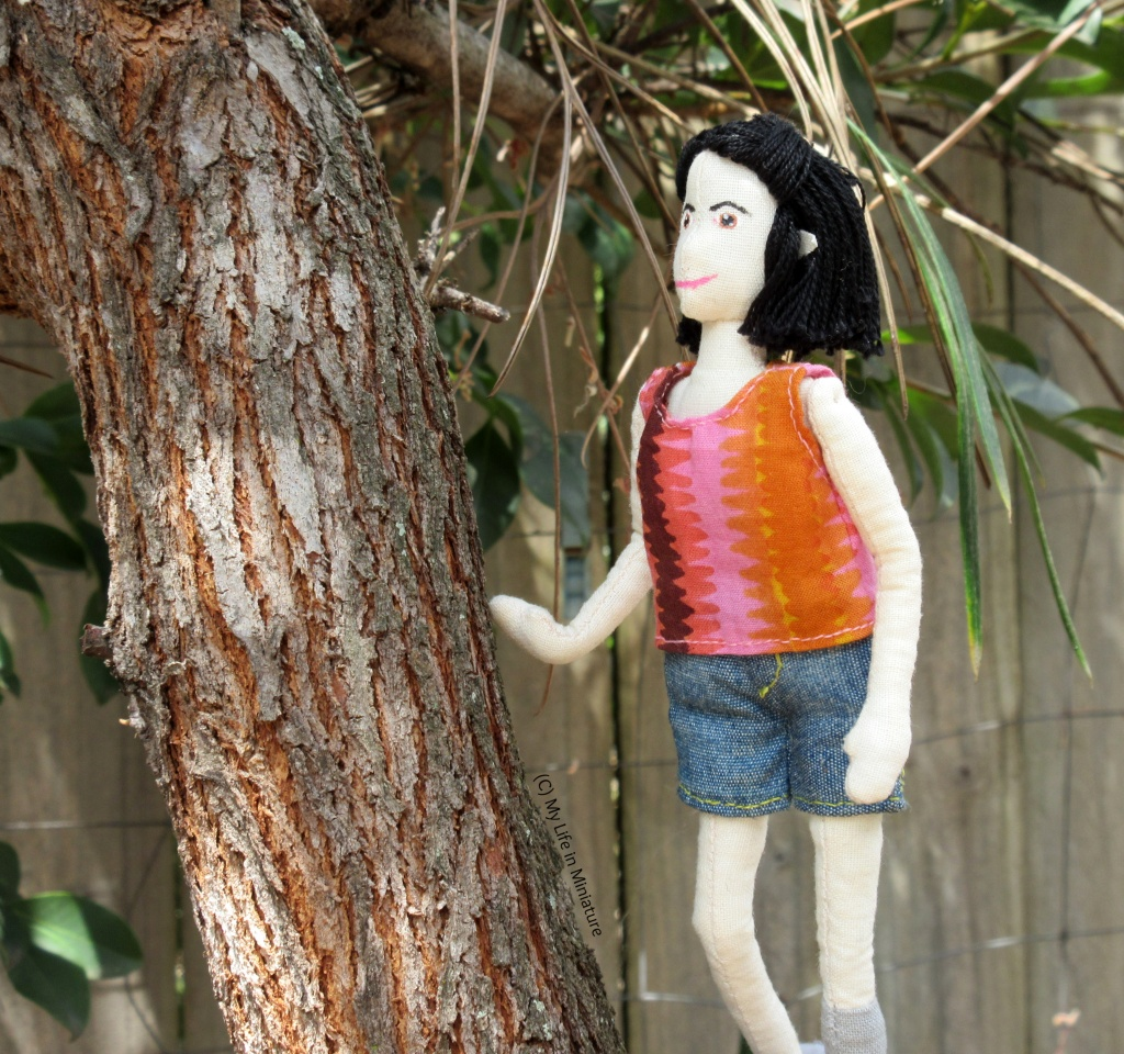 Tiffany stands in a tree fork, one hand on a branch for stability. She looks up the branch at something out of shot.