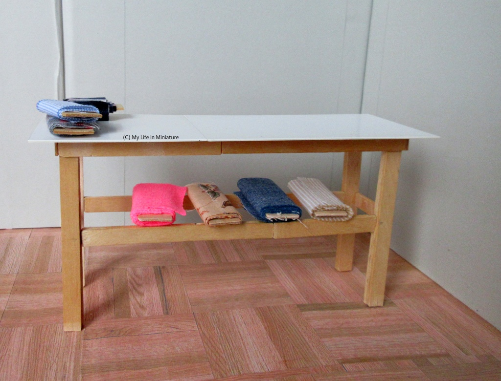 A table, with pale wood legs and a shiny white top, stands against a grey background and on wood parquet flooring. There are three small bolts of fabric on top, and four big bolts underneath.