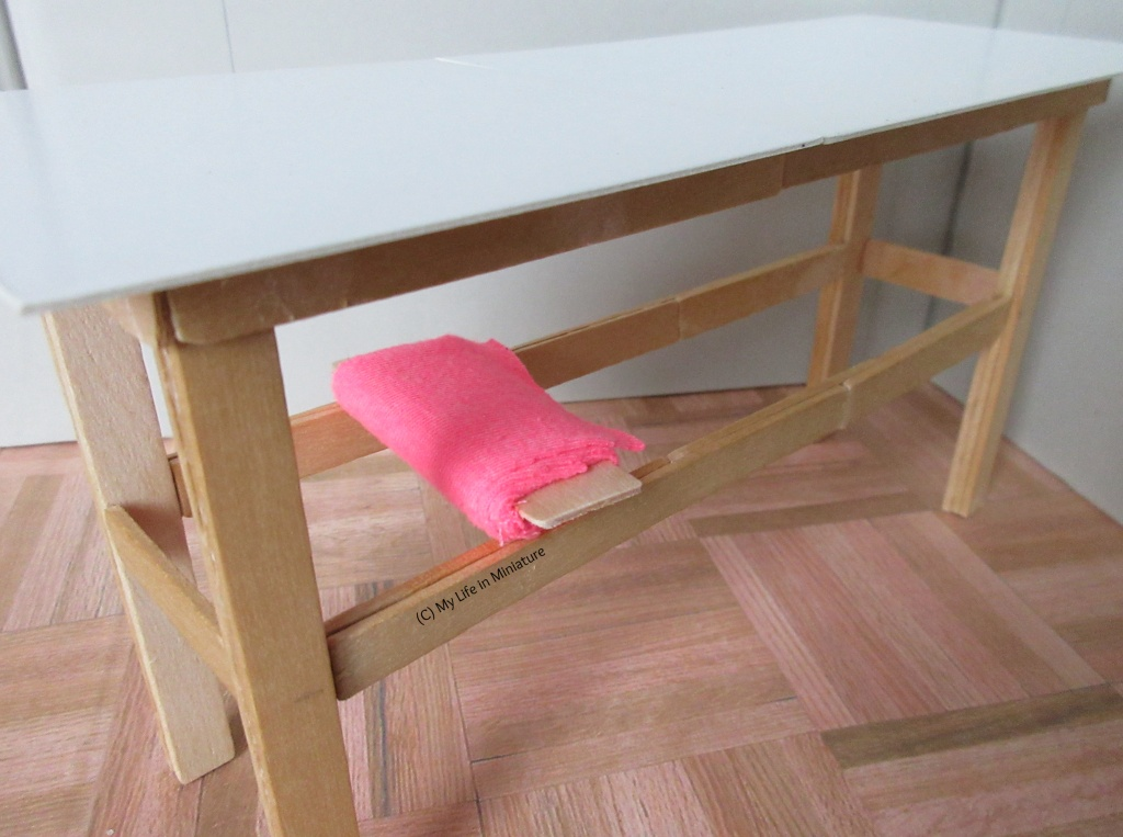 Close-up of a bolt of bright pink fabric resting across two horizontal supports attached to the legs of the table.