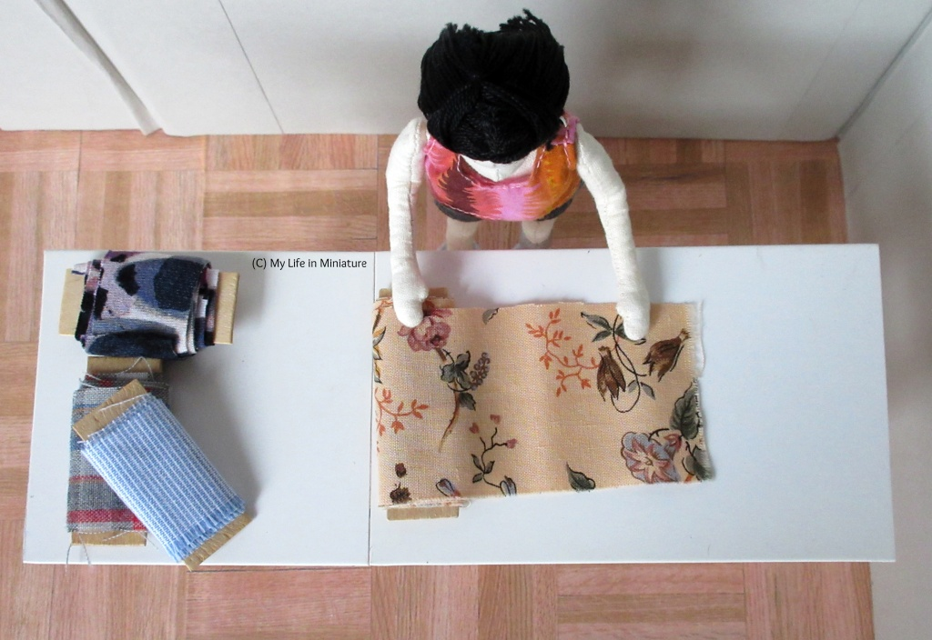 Shot from above of Tiffany rolling out a bolt of fabric on the white top of the table. Three smaller bolts of fabric sit to the left on the table.