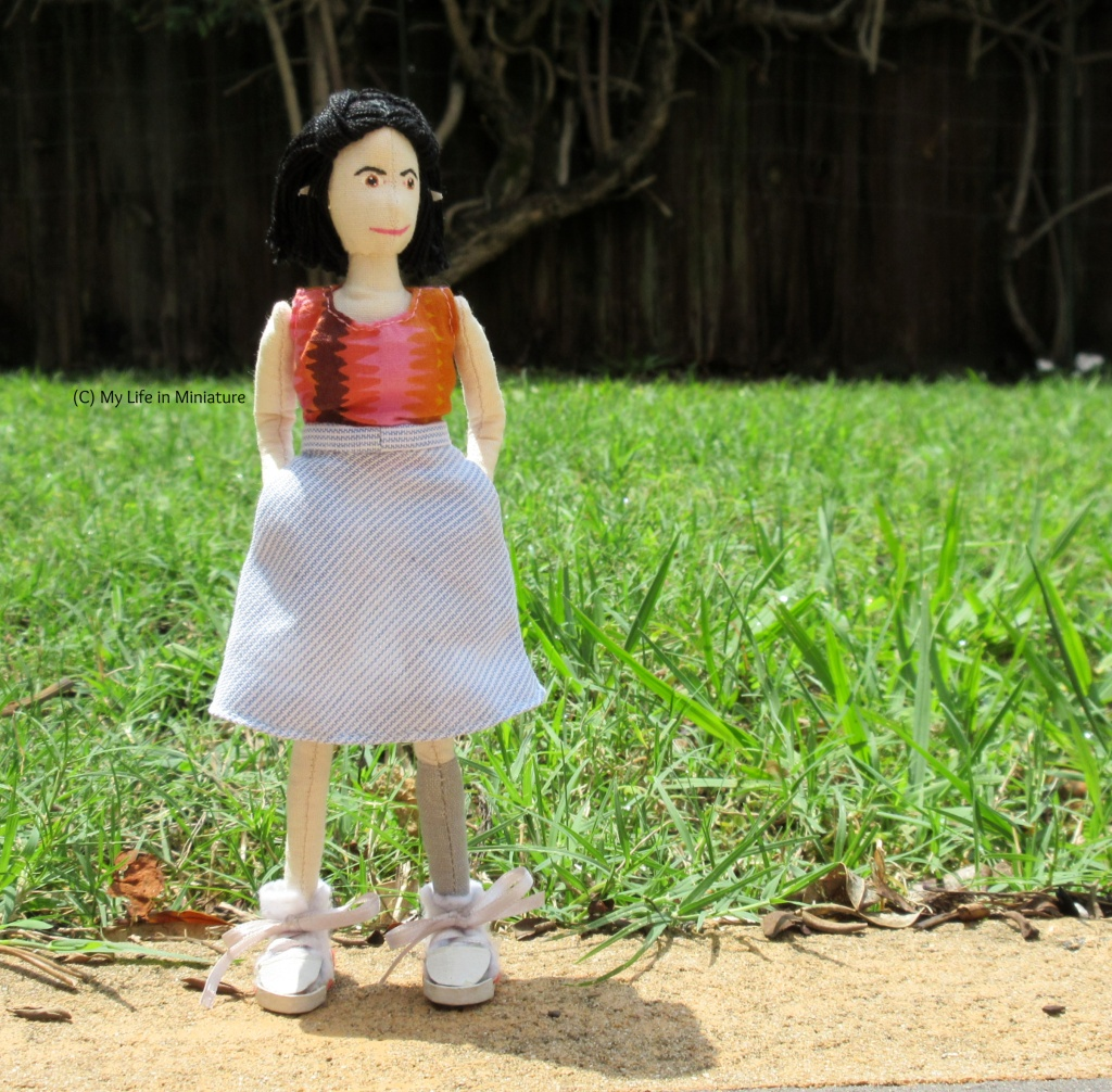 Tiffany stands outside, on the edge of a path, green grass behind her. Her hands are in the pockets of her skirt, and she is looking to the right.