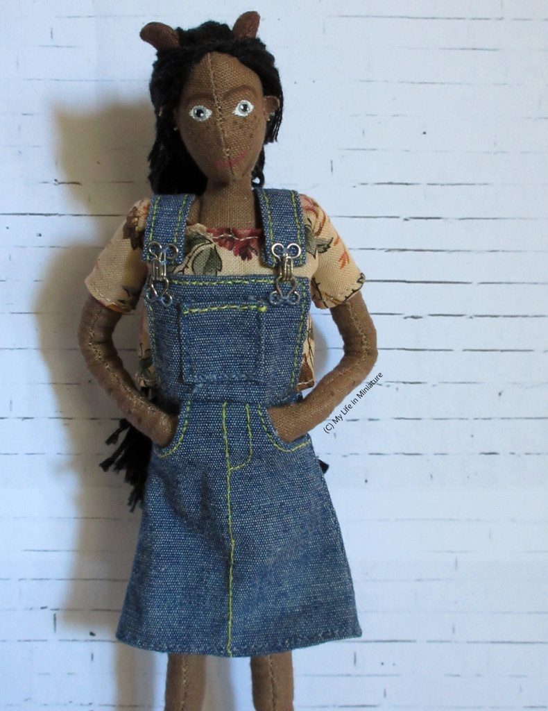 Petra wears a denim skirt with an attached overall-style top, with a front panel and straps over the shoulders. Her hands are in the pockets in the skirt, and she looks at the camera.