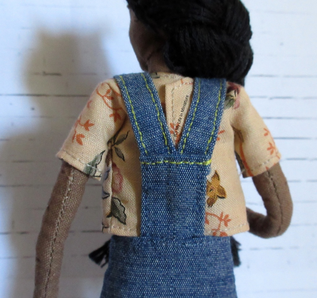 Back view of Petra and the denim overalls. The back has a flat panel attached to the waist of the skirt. The straps are attached to the panel at an angle.