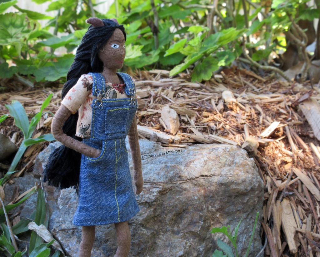 Petra stands beside a rock, a mulched garden bed behind her. She looks to the right and has a hand in the pocket of her skirt.