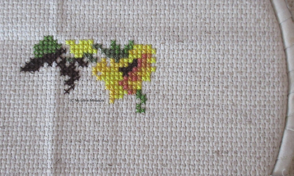 A sunflower head facing down can be seen in cross-stitch on cream fabric. There are also some patches of green and dark brown around and to the left of the flower head.