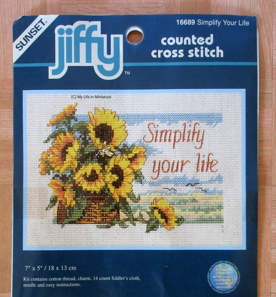 Image of outside paper of a cross-stitch kit. The cross-stitch is of a basket of sunflowers. In the background is some pale trees or grass and some birds. On the right, over the sky, it says 'Simplify your life'.