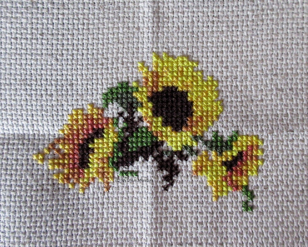Three sunflowers, and greenery between them, are cross-stitched onto cream fabric held in an embroidery hoop.