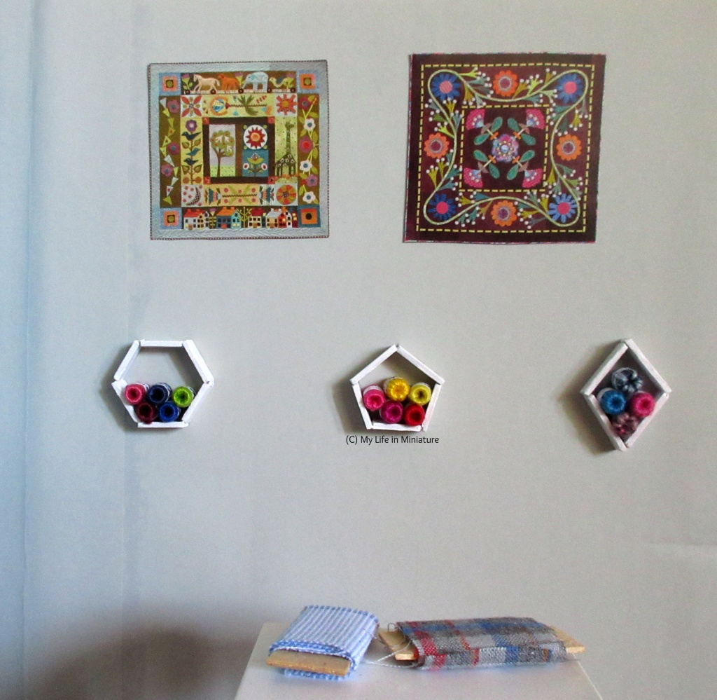 The grey wall beside the fabric table is facing the camera, with the fabric table visible in the foreground. On the wall, there are two images of quilts, and below that is three white shelves stacked with yarn balls.