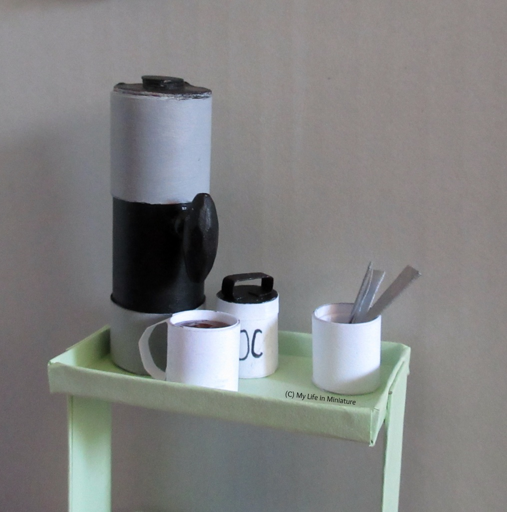 The top tray of the drinks trolley is against a grey background. A white food canister, like a porcelain cookie jar without a lid, sits on top holding silver teaspoons. Also on top is the hot water urn, a mug of hot chocolate, and the white hot chocolate jar.
