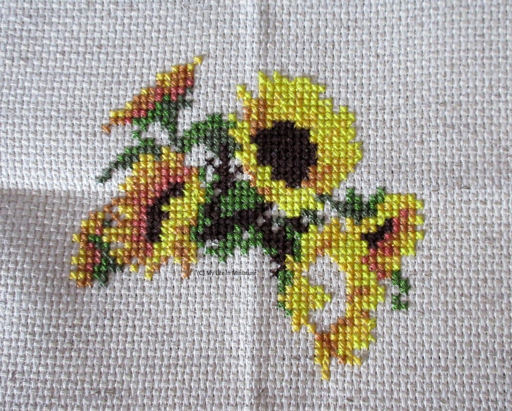 Five-and-a-half sunflowers, and some greenery and stems, are cross-stitched onto cream fabric.