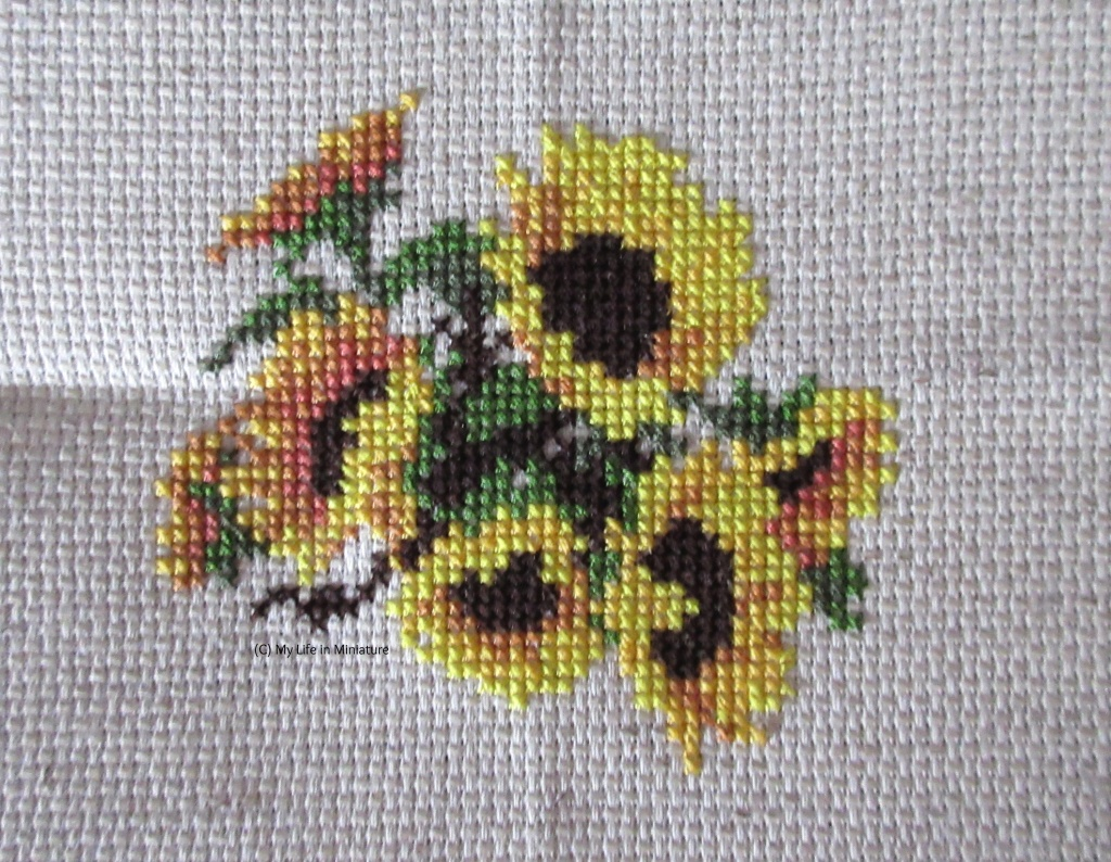 Seven sunflowers, with leaves and stems behind them, are cross-stitched onto cream fabric.