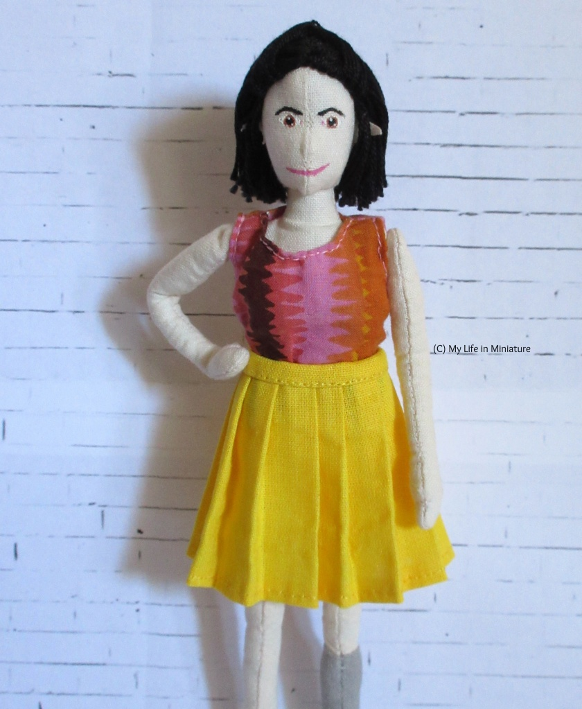 Tiffany stands in front of a white brick background facing the camera. She wears a yellow pleated knee-length skirt, and  a pink-and-orange top. She has a hand on her hip.