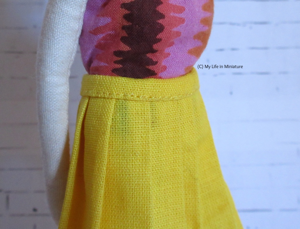 Close-up shot of the waistband of the yellow pleated skirt, to highlight the stitching.