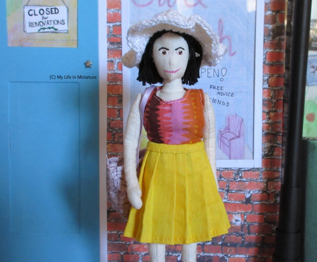 Tiffany stands outside Needle & Thread. She wears the yellow pleated skirt, pink-and-orange top, and a white crocheted sun hat. She carries a pale purple tote bag, and looks straight at the camera.