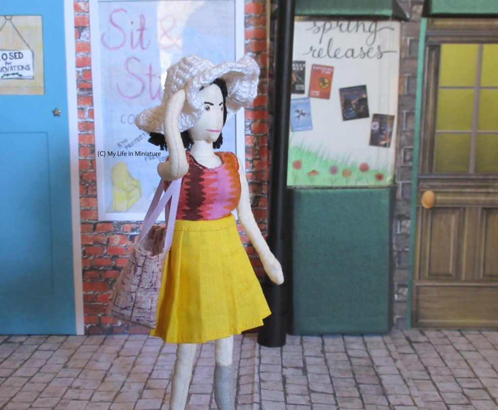 Tiffany stands outside Needle & Thread, facing right. She wears the yellow pleated skirt, pink top, and white sunhat, and carries the purple tote. She has a hand on her hat, like there is a gentle breeze.