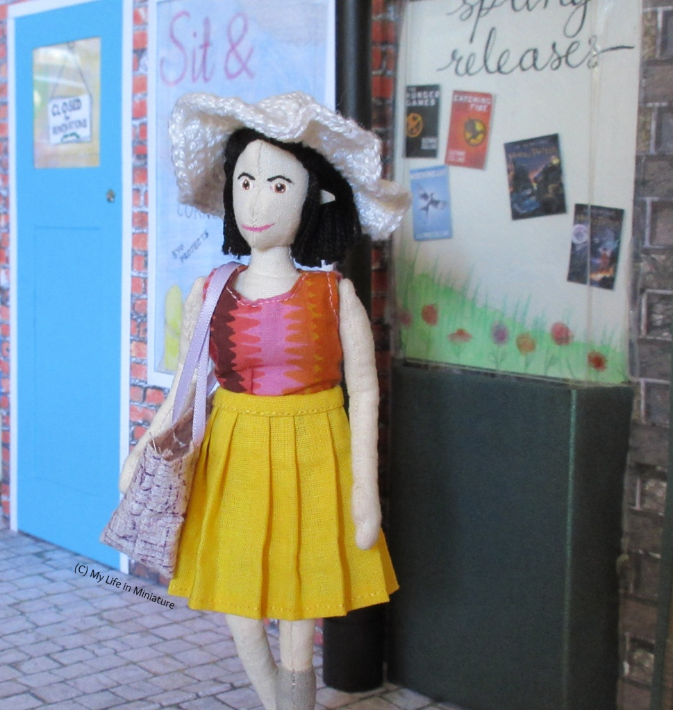 Tiffany stands outside the bookstore, Needle & Thread in the background. She wears the yellow pleated skirt, pink top, and white sunhat. She carries the purple tote and is looking left.
