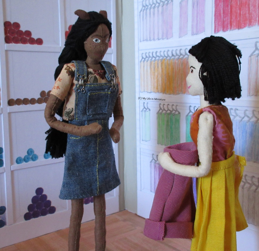 Tiffany holds the completed pair of corduroy shorts to her waist, looking at Petra for her reaction. Petra is clapping her hands together, looking at the shorts. They are in the fat quarters/yarn shelves corner of Needle & Thread.