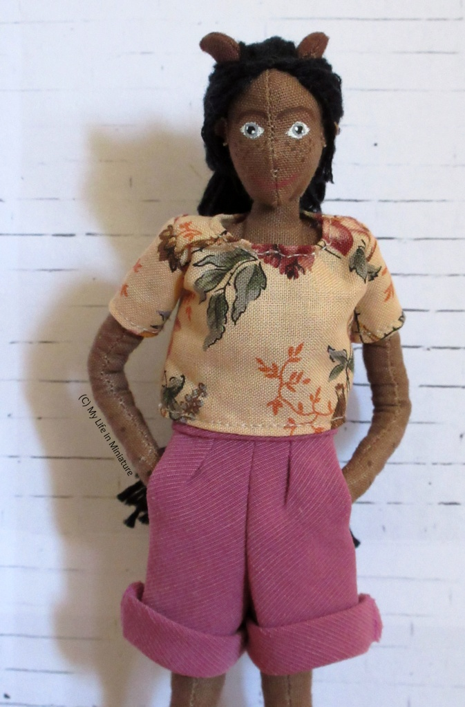 Petra looks at the camera, hands in pockets of her dusky pink corduroy shorts. There are two pleats in the front of the pants, and the bottom hems are rolled up. She wears her cream floral t-shirt, and stands in front of a white brick background.