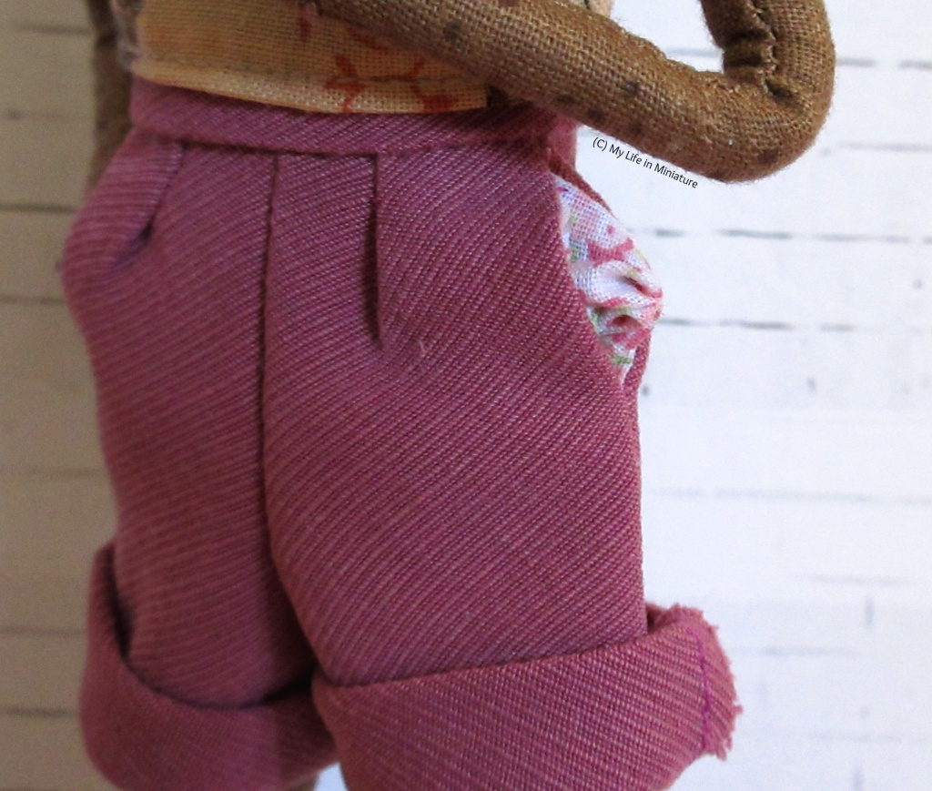 Close-up of the partially-pulled-out pocket of the shorts, which is pulled out to show the pink floral pattern on the pocket inside.