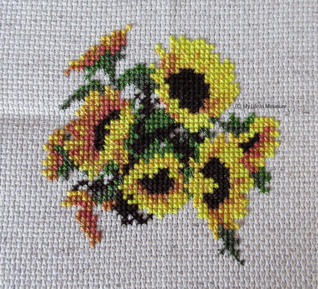 Seven complete sunflowers and the beginnings of an eighth are cross-stitched onto cream fabric, with green leaves around and in-between them.