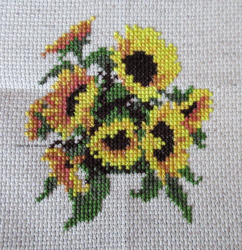 Eight sunflowers and their leaves are cross-stitched onto cream fabric.