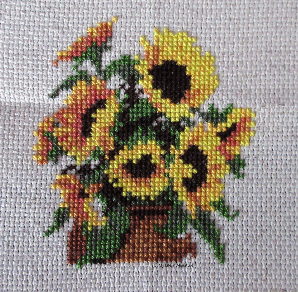 Eight sunflowers, their leaves and stems, and a brown basket beneath them are cross-stitched onto cream fabric.