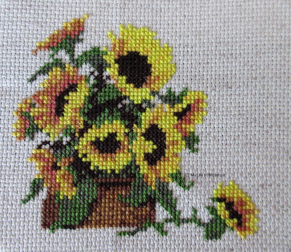 Eight sunflowers in a basket are cross-stitched onto cream fabric. In front of the basket is a ninth sunflower (with stem and leaves) that has fallen out of the basket, cross-stitched.