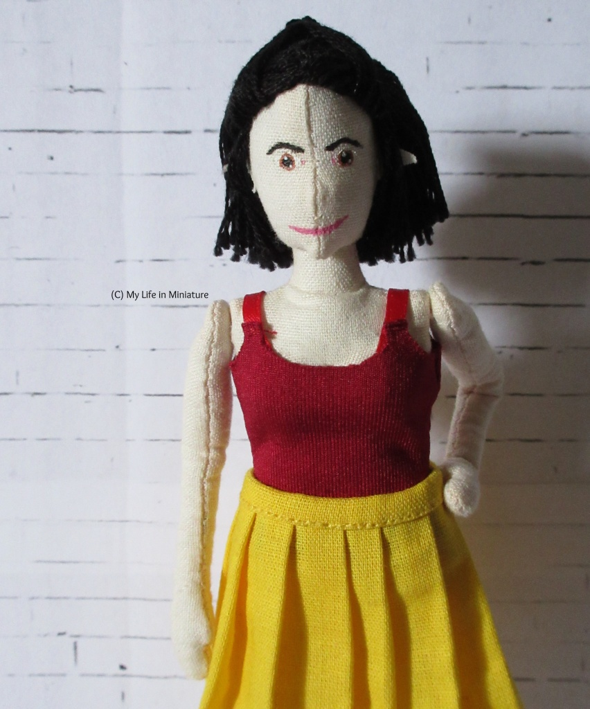 Tiffany wears a dark red jersey scoop-necked singlet top, which has red ribbon for straps. She also wears the yellow pleated skirt, and stands with a hand on hip in front of a white brick background.
