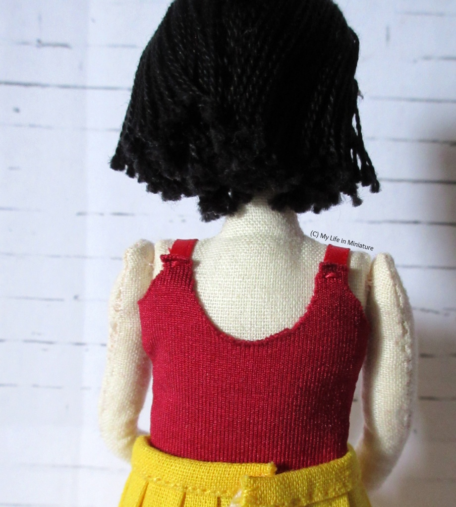 Back view of the singlet top Tiffany is wearing, showing the deeper scoop-neck, and lack of velcro fastening. The back of Tiffany's head can be seen too, against a white brick background.