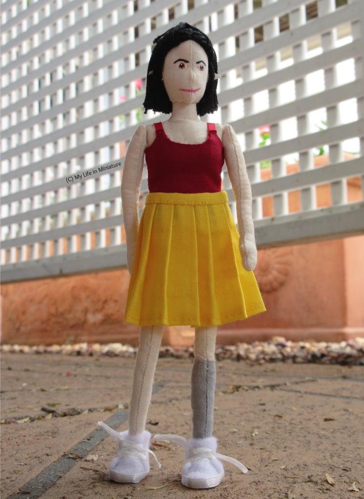 Tiffany stands on a terracotta concrete slab, with a white lattice and large terracotta pots in the background. She wears the dark red singlet and yellow pleated skirt, has both hands hanging at her sides, and looks to the right middle distance. The angle of the shot is low, looking up at her.