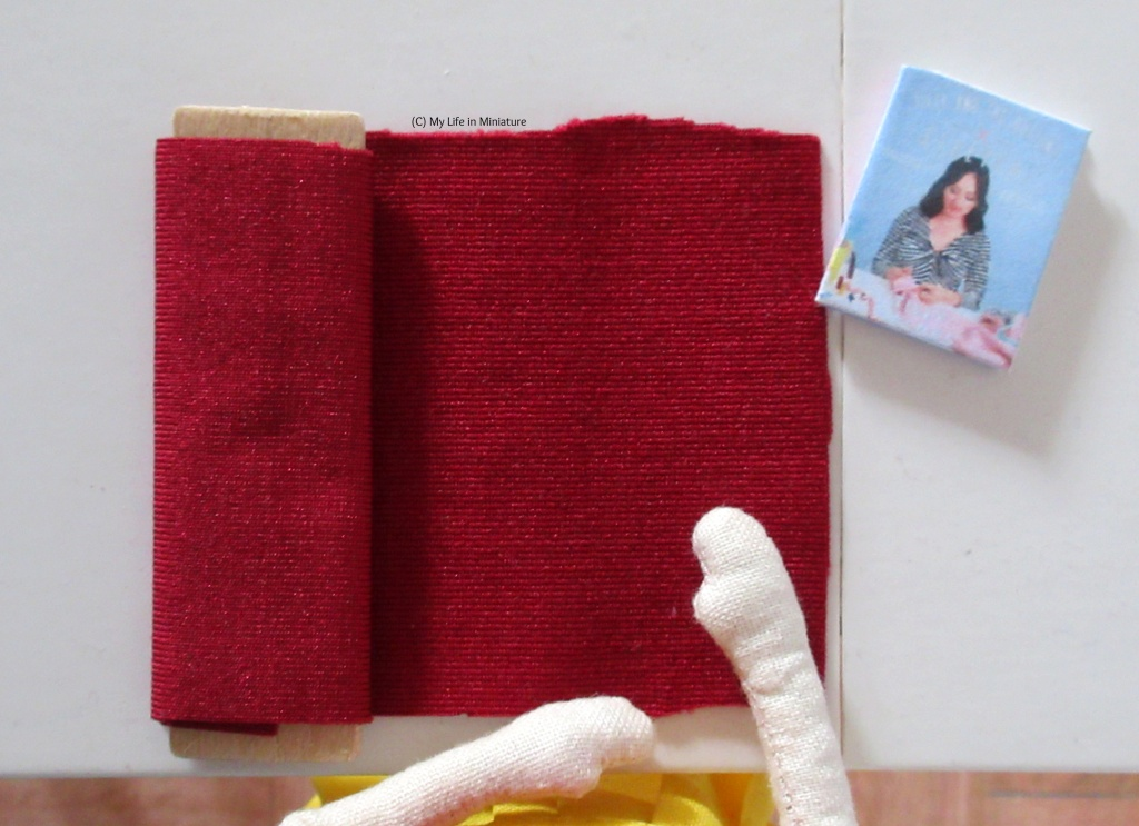 Overhead shot of the Needle & Thread fabric table. On it is a bolt of thick dark red jersey, partially unravelled, and a sewing book to the top right. Tiffany's hands are visible resting on the laid-out jersey.