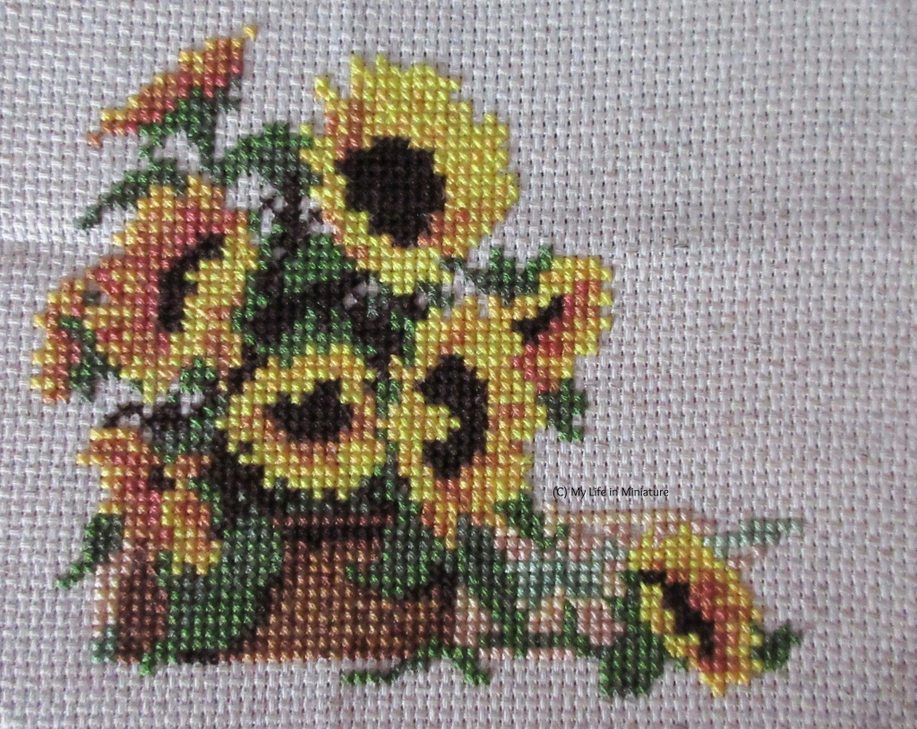 Nine sunflowers in a brown basket are cross-stitched onto cream fabric. The beginnings of a background are behind the flower in the foreground, in pastel shades of pink, yellow, and green.