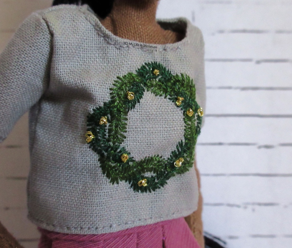 Close-up of the wreath on Petra's t-shirt. Two branches, embroidered in different shades of green, are visible in detail. Also visible are the gold knots scattered around the wreath.