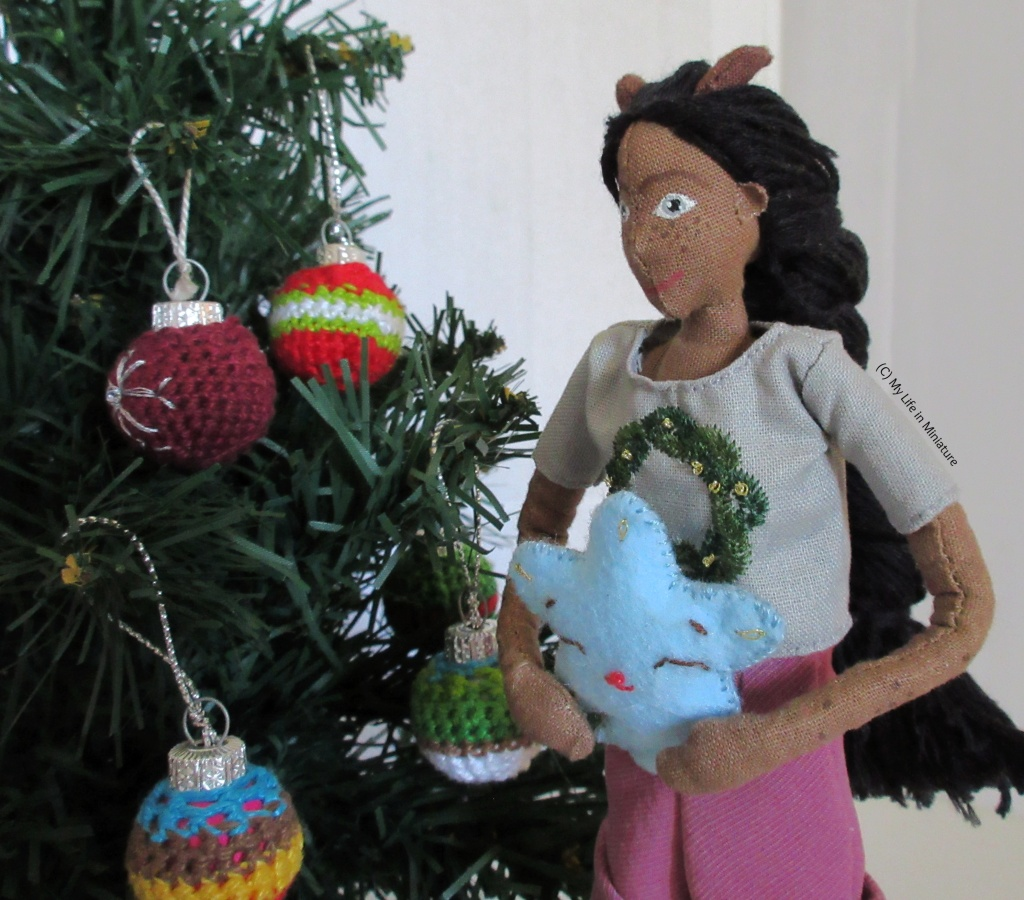 Petra stands to the right of the tree, holding a blue felt star. She is looking down at it as she faces to the left of the shot.
