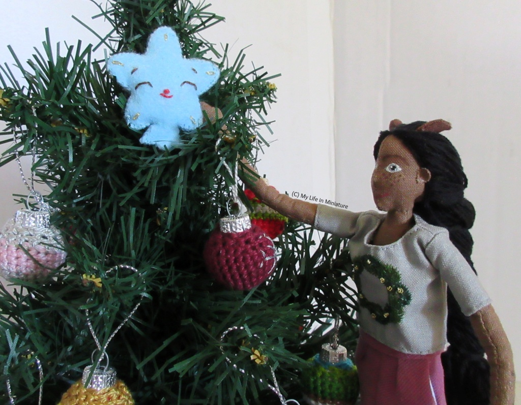 Petra stands to the right of the tree, looking up at the top of it. One arm is extended, putting the star at the top of the tree. Her other arm hangs at her side.