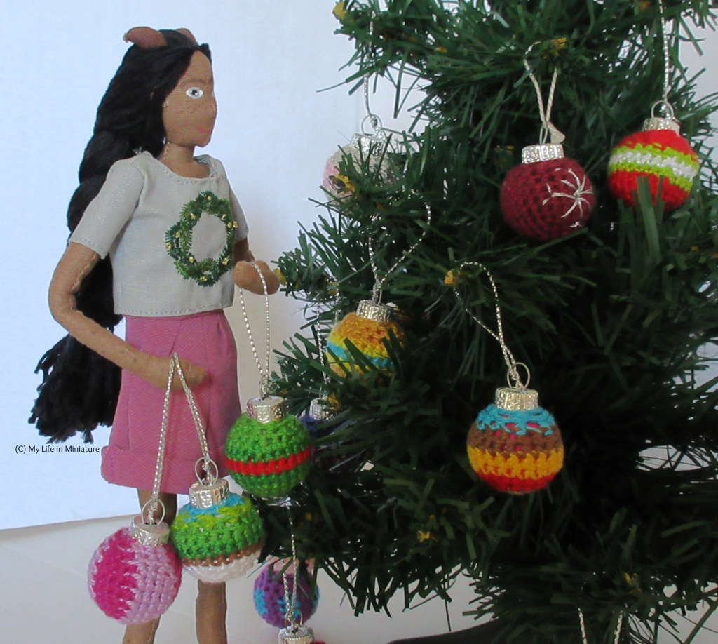 Petra stands to the left of a to-scale Christmas tree. She wears the wreath t-shirt and is carrying three baubles, looking for where to hang them. The tree has a few baubles on, but still some empty spaces.